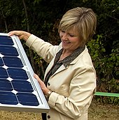 Former PGE CEO Peggy Fowler in a portrait with a solar panel.