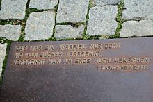 """Plaque at the Nazi book burning memorial on Bebelplatz in Berlin, Germany. The plaque has a quote from Heinrich Heine's play Almansor (play, written 1821–1822). """"Where they burn books, in the end they will also burn human beings"""" (Dort, wo man Bücher verbrennt, verbrennt man am Ende auch Menschen) about burning of Quran in Granada that was expected to be followed by burning humans (Muslims then Jewish) in 1500s. (Source: Wikimedia)"""