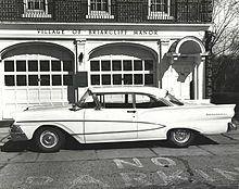 1960s white sedan parked in front of a brick building