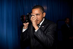 President Barack Obama takes aim with a photog...