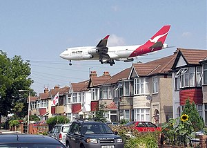 Takeoff and landing - A landing Qantas Boeing 747-400 passes close to houses on the boundary of London Heathrow Airport, England