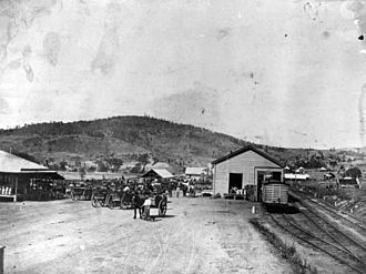 Somerset Region - Horse-drawn wagons at the Lowood Railway Station with the Queensland Farmer's Co-Op. Ltd on the opposite side of the street.