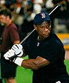 "A dark-skinned man in a dark blue shirt. He is holding a black baseball bat over his shoulder in both hands. He is wearing a navy blue baseball cap with a red ""B"" outlined in white, and the same ""B"" logo is shown on his shirt at the neck."