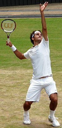 A dark-haired man is in the serving motion, which he is in all white clothing, and he has a reddish-black tennis racket in his right hand