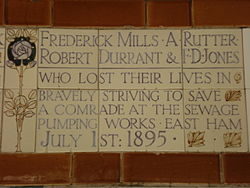 "A tablet formed of five tiles of varying sizes, bordered by yellow and blue flowers in an art nouveau style. The tablet reads ""Frederick Mills, A Rutter, Robert Durant & F. D. Jones who lost their lives in bravely striving to save a comrade at the sewage pumping works, East Ham July 1st 1895""."