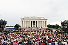 Trump addressing the crowd at the Lincoln Memorial. An M2 Bradley tank can be seen either side of him.