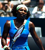 A black woman with a blue dress holding a tennis racket out in front of her