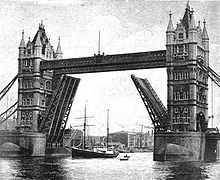 A ship with two tall masts is passing beneath the raised carriageways of a road bridge. The bridge has twin ornamental stone towers which are connected by a walkway high above the river.