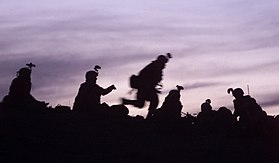 Soldiers from the 10th Mountain Division (Light Infantry), participating in the Combined Joint Task Force Mountain's Operation Anaconda, prepare to dig into fighting positions after a day of reacting to enemy fire, March 2002.jpg