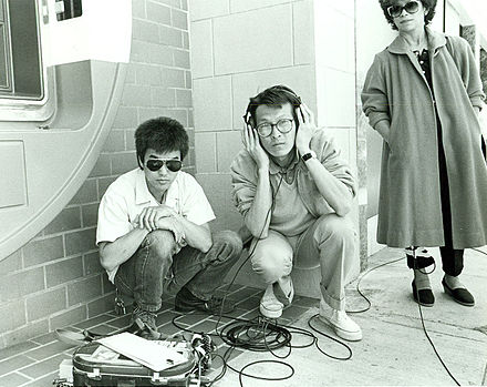 Sound recordist Curtis Choy (left) on location for Dim Sum: a Little Bit of Heart, an indie film by director Wayne Wang (center) on Clement Street in the Richmond District of San Francisco, California 1983 Sound recordist Curtis Choy.jpg