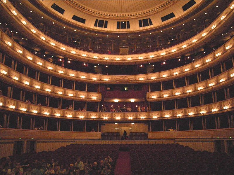 View from the stage of the auditorium of an opera house with red seats and gold lights.