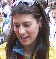 Front on image of a smiling, brown haired young woman with hair longer than her shoulders, pearl spherical earrings with sunglasses on her hair which is parted down the middle, wearing a yellow jacket tracksuit with a green collar, with a red medal ribbon around her neck.