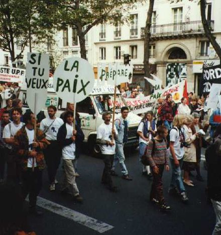 "Demonstration against French nuclear tests in 1995 in Paris ""This interaction can take the form of ... basic ""street rhetoric"" that ""open[s] a dialogue between competing factions"". StopEssaisManif.jpg"