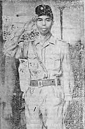 A man, saluting; he is wearing a military uniform and peci.