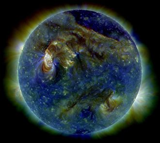 Sun - In this false-color ultraviolet image, the Sun shows a C3-class solar flare (white area on upper left), a solar tsunami (wave-like structure, upper right) and multiple filaments of plasma following a magnetic field, rising from the stellar surface.