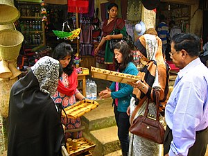 Chittagong Hill Tracts - A Chakma shop with handicrafts on display, and a small crowd of tourists. The Hill region is a tourist attraction in Bangladesh.