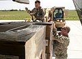 U.S. Army Sgt. Matthew Tullis, in forklift, with the 1245th Transportation Company, 90th Troop Command, Oklahoma Army National Guard, waits as Chief Warrant Officer 3 Dustin McNeeley, left, and Chief Warrant 130523-Z-TK779-032.jpg