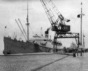 A photograph of a ship tied up to a pier. The bow of the ship points toward the left of the frame. On the right of the frame is an overhead crane.