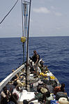 U.S. Navy and Marine Corps visit, board, search and seizure team members stationed aboard the guided missile cruiser USS San Jacinto (CG 56) stand guard over suspected pirates on board a dhow as they travel 100527-N-EF447-197.jpg