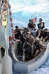 U.S. Sailors and Marines with the visit, board, search and seizure team, currently assigned to the guided missile cruiser USS San Jacinto (CG 56), complete loading of a rigid-hull inflatable boat in preparation 100524-N-EF447-007.jpg