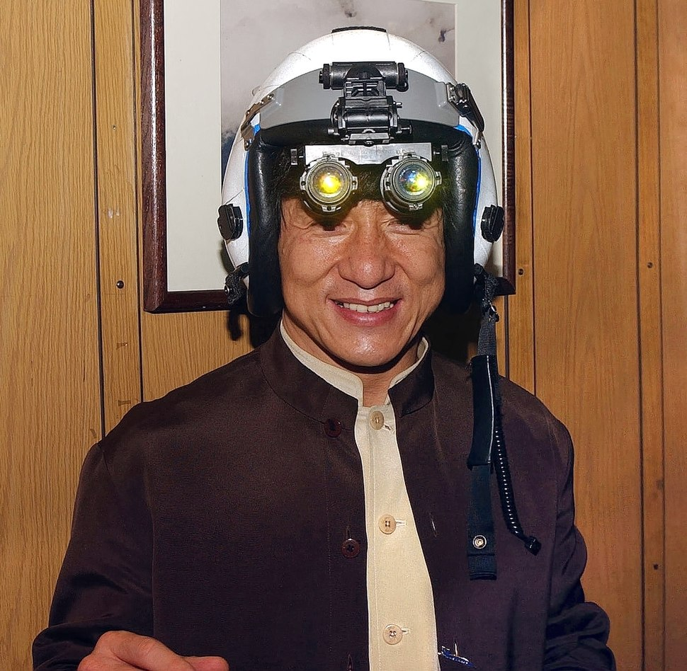 US Navy 021202-N-0271M-016 Jackie Chan tries on a fighter pilot%27s helmet with night vision goggles attached during his visit aboard USS Kitty Hawk (cropped)