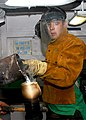 US Navy 031020-N-2325K-001 Aviation Boatswain's Mate Christopher Branscome, from Hillsboro, Ohio, pours 975 degrees Fahrenheit zinc into a topside arresting gear terminal aboard USS George Washington (CVN 73).jpg