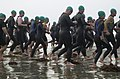 US Navy 040925-N-7949W-012 Superfrog Triathlon competitors run through the kelp toward the ocean at the beginning of the swim portion of the race.jpg