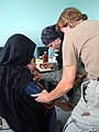 US Navy 070822-F-8346E-002 U.S. Air Force Maj. Debra Roberts, center, and U.S. Navy Lt. Karen Nordine check vital signs on an Afghan woman and her child during a village medical outreach in Shinkay District.jpg
