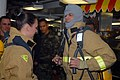 US Navy 071205-N-6516T-180 Damage Controlman Fireman Dalena Powell helps TV and film star Johnny Knoxville don fire fighting equipment on the aft mess deck aboard the nuclear-powered aircraft carrier USS Nimitz.jpg