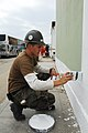 US Navy 080614-N-6410J-043 Utilitiesman 3rd Class Jeffrey Schuett, assigned to Navy Mobile Construction Battalion (NMCB) 5 embarked aboard the amphibious assault ship USS Boxer (LHD 4), paints the trim on a building.jpg