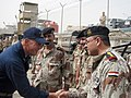US Navy 081308-N-5068C-015 Lt. Cmdr. Trent Thompson, commanding officer of the coastal patrol boat USS Firebolt (PC 10), greets senior Iraqi naval officers on the pier after the boat arrives in Umm Qasr as part of Iraq Navy Day.jpg