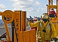 US Navy 090718-N-9950J-400 Aviation Boatswain's Mate (Handling) Airman Jessie Washington directs a forklift on the flight deck of the forward-deployed amphibious assault ship USS Essex (LHD 2) during a vertical replenishment.jpg