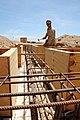 US Navy 100501-N-8936G-043 Builder 2nd Class David Harwell, from Fort Worth, Texas assigned to Naval Mobile Construction Battalion (NMCB) 7, shores up the foundation formwork of the new schoolhouse in Kontali.jpg