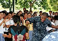 US Navy 101014-N-7783B-035 U.S. Navy Musician 3rd Class Michael Bookman, assigned to the U.S. 7th Fleet Band, Orient Express, dances with students.jpg
