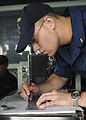 US Navy 110515-N-YM590-086 Ensign Austin E. Ayres plots the ship's position on a maneuvering board on the bridge of the guided-missile cruiser USS.jpg