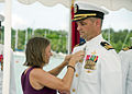 US Navy 110722-N-AZ907-055 Erica Kraft, left, pins the Command at Sea pin on her husband, Cmdr. Scott H. Kraft.jpg