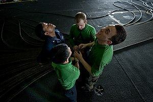 US Navy 120130-N-BT887-391 Sailors check the overhead in the hangar bay for a place to send an arresting gear cable aboard the Nimitz-class aircraf.jpg