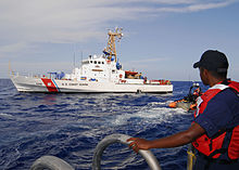 a boatswains mate watches from the side port door as coast guard cutter bertholfs over the horizon small boat departs to receive personnel from coast