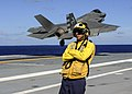 VX-23 F-35C Lighting II taking off during touch-and-go landing on USS George Washington (CVN-73) watched by plane handler (160820-N-VH385-826).jpg