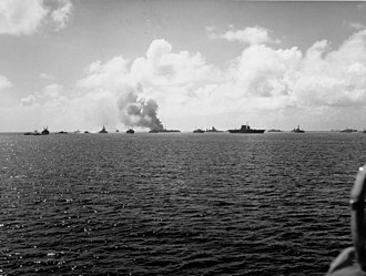 Operation Crossroads - The target fleet after test Able. The aircraft carrier Saratoga is in the center with Independence burning at left-center. The ex-Japanese battleship Nagato is between them. Note the ship at left next to the battleship Pennsylvania trying to wash down the radioactivity with water from the lagoon.