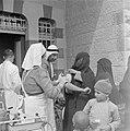 Volwassenen en kinderen in een polikliniek terwijl een vrouwelijke verpleegkundi, Bestanddeelnr 255-0949.jpg