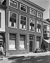 foto van Huis met statige lijstgevel tegen de pui modern beklampt met in de verdieping empire-schuiframen en in de mezzanino draairamen