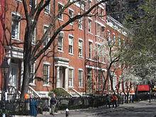Un'inquadratura lunga di un condominio di media altezza sul lato della strada.  L'edificio ha cancelli e alberi nella parte anteriore, con alberi sporgenti sulla strada e pedoni che camminano sul marciapiede.