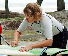 Photo of woman bent over surfboard rubbing bar of solid wax against the board with palm trees and ocean in background