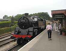 Steam locomotive (number 80136) with carriages at station platform.