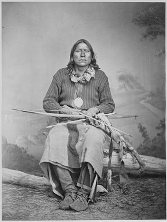 Satanta (chief) - Satanta (White Bear), Kiowa chief, full-length, seated, holding bow and arrows and showing his presidential medal but not wearing his famous military jacket