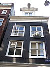 foto van Hoekhuis waarvan de voorgevel en de gepleisterde zijgevel door de omlopende lijst van het toen aangebrachte dak worden beëindigd