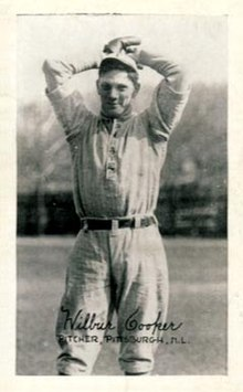 A man wearing a lightly colored baseball uniform holds his hands above his head, winding up to throw.