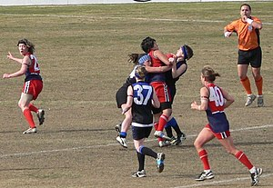 "Holding the ball - A Women's Australian rules football player is caught ""holding the ball"", wrapped up in a gang tackle by two opponents. The field umpire (in orange) is about to signal ""holding the ball"" to penalise the player in possession and award a free kick to the first tackler."