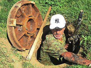 Sanitary sewer - Manhole access to sewer; person shows scale